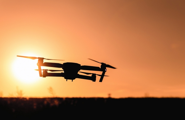 A drone flying at sunset.