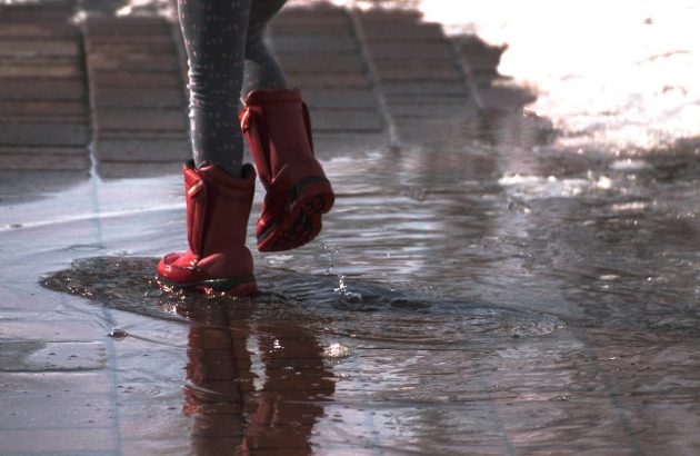 The lower half of a child wearing red rainboots and splashing in a puddle on a brick street.