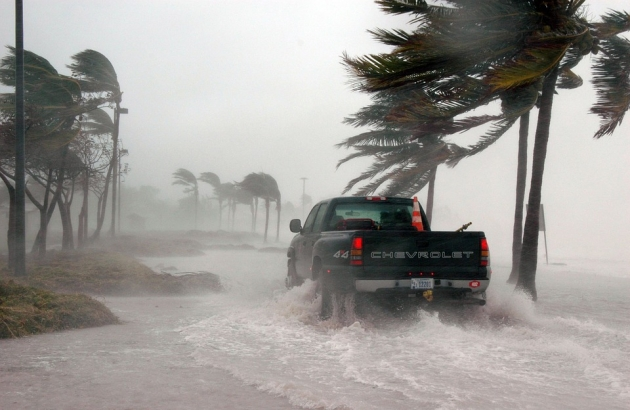 A truck driving through a water filled street in a hurricane.