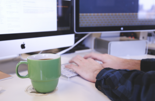 Person typing at a computer. A green mug sits next to their left hand.